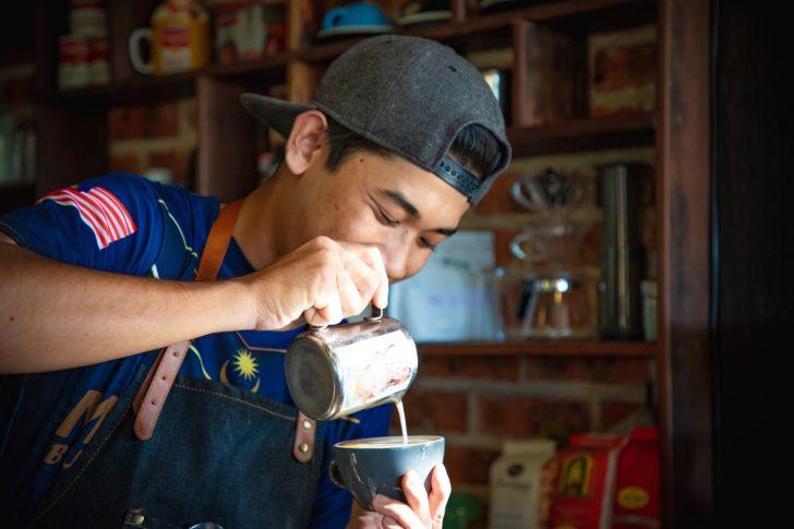 笑顔でコーヒーを淹れる男性の画像