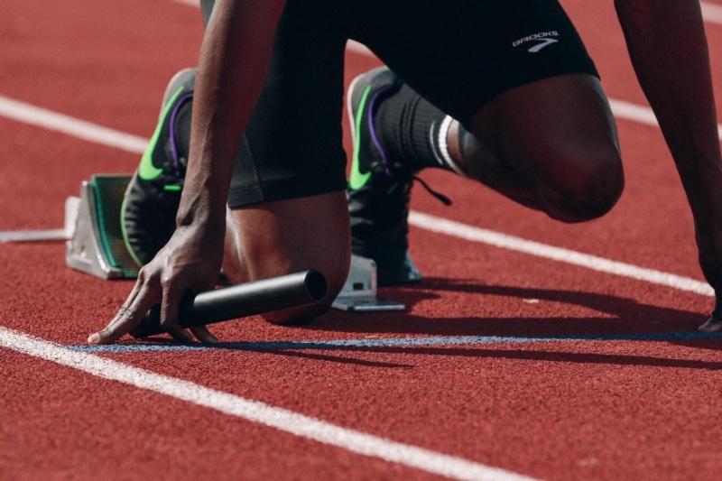 スタートの位置で構える短距離走選手の画像